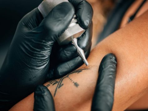 Closeup of tattoo and needle, via Getty Images.