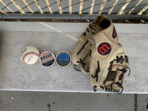 A baseball glove, a baseball, and two cans of chewing tobacco.