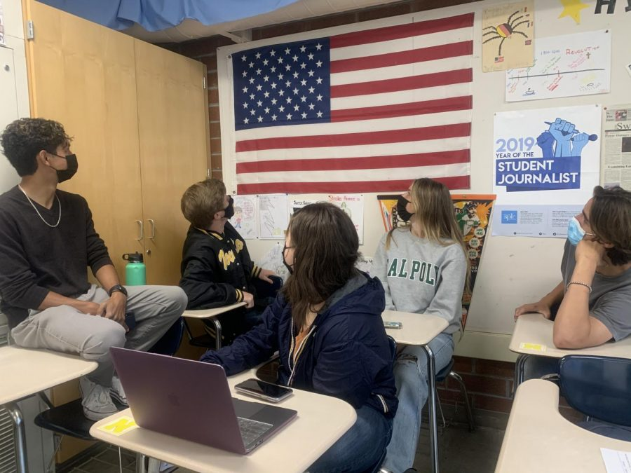 Students look at an American flag in a classroom.